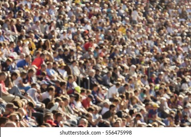 Blurred out people attending an event at an outdoor stadium