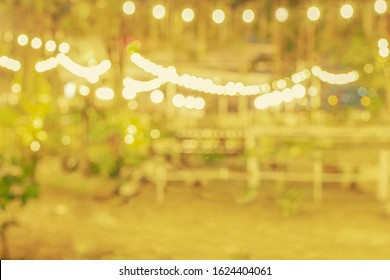 Blurred outdoor dining area of local restaurant decorated with abstract bokeh string lights. Use for background, montage product display or design key visual layout. Copy space.