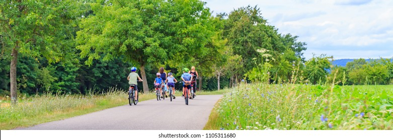 Blurred panoramic background with Children and mothers on bikes on asphalt road among grass and trees, Germany