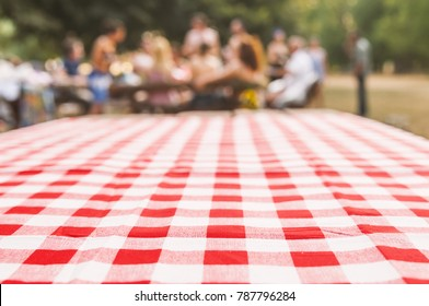 blurred party on background, fun / spring concept. Red checkered tablecloth texture top view with abstract green bokeh from garden. Abstract blur people picnic in the park.  Blurred concept.