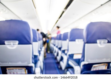 blurred passenger and airhostess standing in the airplane