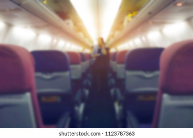Blurred passenger walking interior of airplane with empty seats and stewardess walking the aisle in background. Travel concept, vintage color filter