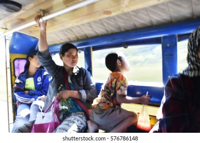 blurred peasantry passengers holding on to the poles,sitting down in the car. It is slightly blurred as it is moving down the road,journey in the countryside of Thailand.