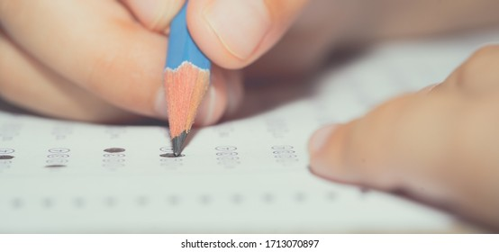 Blurred pencil lead on hand student holding to make answer on multiple choice of question assessment examination in classroom of school