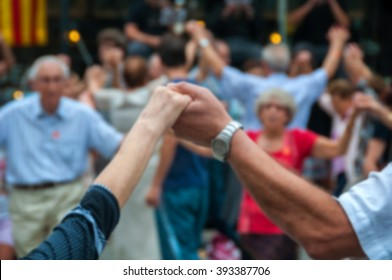 Blurred people backgrounds - senior people holding hands and dancing national dance Sardana at Plaza Nova, Barcelona, Spain. It is a type of circle dance typical of Catalonia.