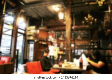 Blurred people in bar are relaxing and drinking happily