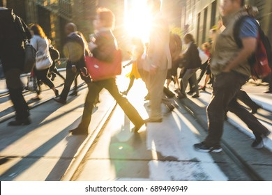 Blurred people crossing the street. Background ready image with fast moving people walking across the road in Toronto with sun flares in the middle. Travel and commuting concepts