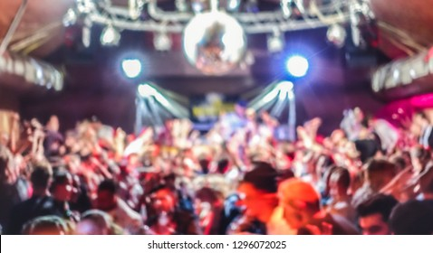 Blurred people dancing at music concert event - Abstract defocused background of disco club after party at live stage festival - Nightlife entertainment concept - Bright spotlight filter