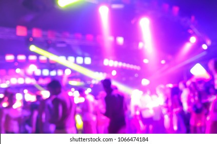Blurred people dancing at music night festival event - Abtsract defocused image background of disco club after party with laser show - Nightlife entertainment concept - Bright marsala spotlight filter