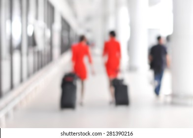 Blurred people and flight attendants walking at the airport hallway
