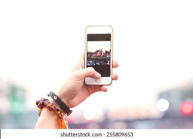 blurred people hand hold phone take photo in concert and travel up to sky with purple light background, internet and communication lifestyle.
