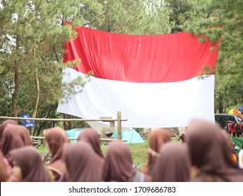 blurred people and huge Indonesian flag