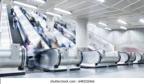 blurred people on escalators
