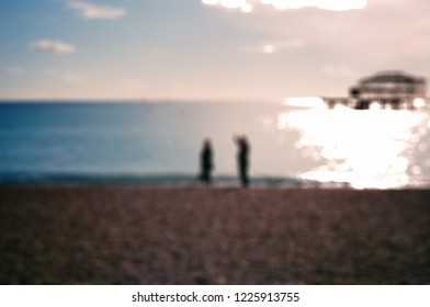 Blurred people on sand beach with sun beams background