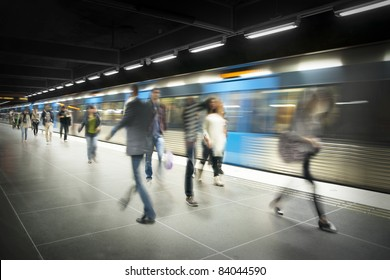 Blurred people on subway platform with moving blue train