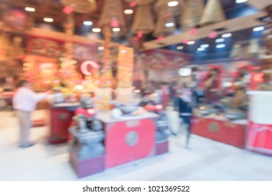 Blurred people pray inside Hong Kong template in Houston, Texas, USA. Incense offerings and coils suspended from the ceiling