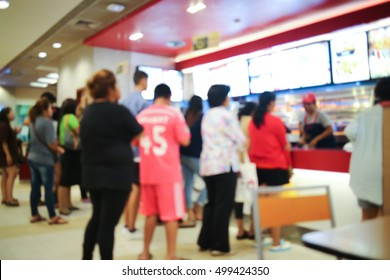 Blurred people queue up waiting in line to buy fast food.
