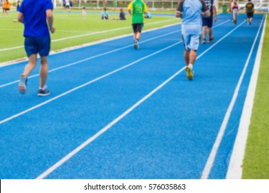 blurred - people running on a running track blue color - Use For fitness or competition.