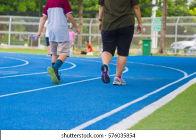 blurred - people running and walking on a blue running track - use for fitness or competition.