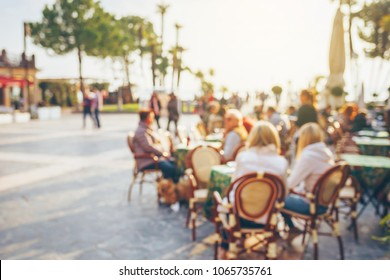 Blurred people sitting at the table in street cafe.