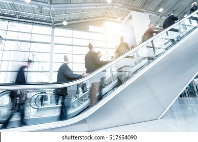 blurred people using a skywalk/staircase at a traid fair