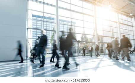 blurred people walking in a modern hall