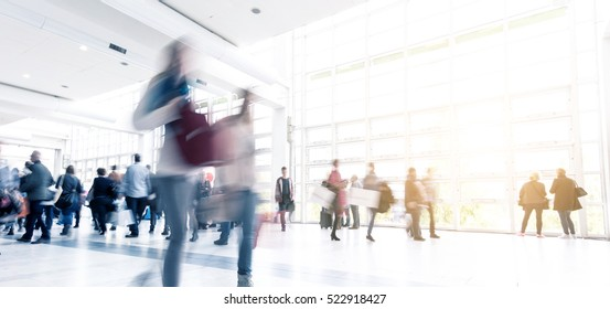 blurred people walking in a modern hall