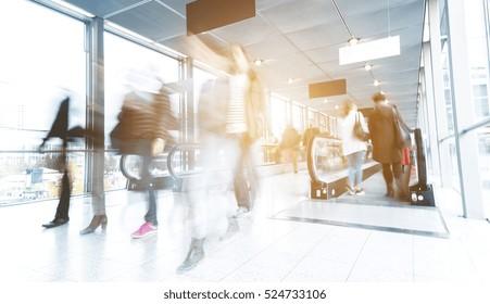 blurred people walking in a modern traid fair entrance