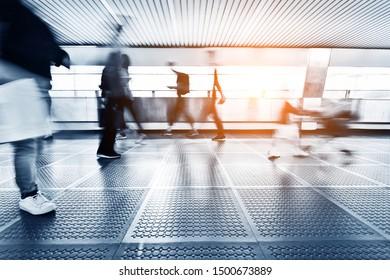 Blurred people walking on footbridge.