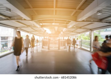 Blurred people walking on sky-walk under electric train station in Bangkok City, Thailand - City Concept