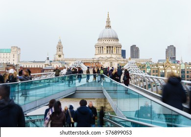Blurred people walking over Millennium bridge at cold winter day. St Pauls cathedral in the background