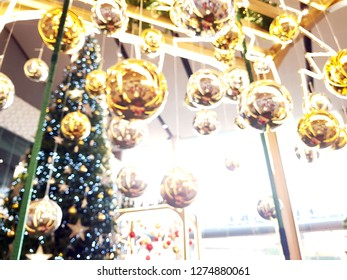 Blurred phot of Christmas accessories hanging on decorated with lights Christmas tree.