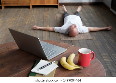 Blurred phot of senior caucasian man meditating on a wooden floor of living room and lying in Shavasana pose after practice. Table with laptop, banana and cup on the foreground