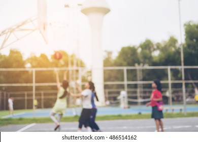 Blurred photo of Asian children are playing basketball with warm sun light from top right corner