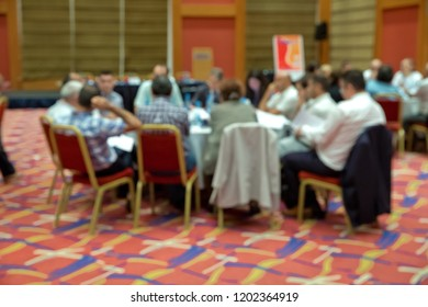 Blurred photo of audience group attending in conference meeting room. Group of business people attending press conference or presentation.