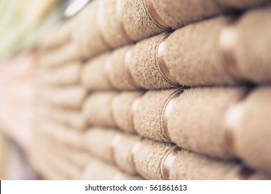 Blurred photo of Big shelf with a beige stack towels.
