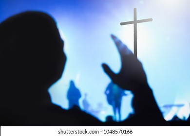 Blurred photo of Christian worship God together in Church hall in front of music stage and light bokeh effected.raised hand and praise the LORD.Good friday and worship concert background.