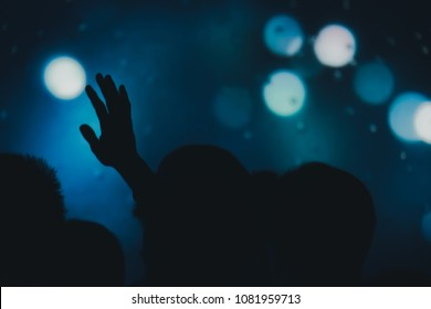 Blurred photo of Christian worship God together in Church  and light bokeh effect.raised hand and praise the LORD. concert background.