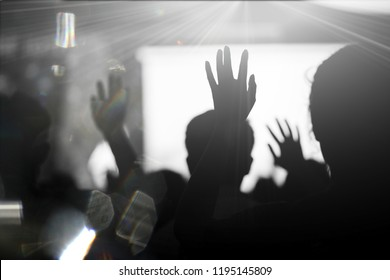 Blurred photo of Christian worship God together in Church hall in front of music stage.raised hand and praise the LORD.Music concert background.