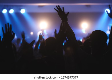 Blurred photo of Christian worship God together in Church ,raised hand and praise the LORD ,concert background.