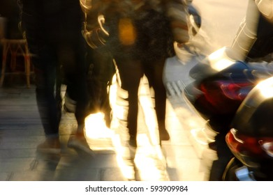 Blurred photo of couple on Parisian street in sunny winter day passing between cafe tables and motorbikes. Abstract urban concept.