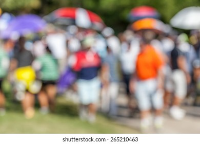 Blurred photo of golfer and audience on green in golf tournament.