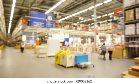 Blurred photo of interior of warehouse. Rows of shelves with boxes and shoppers.