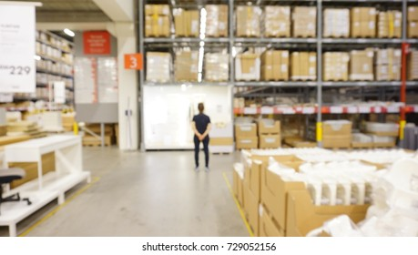 Blurred photo of interior of warehouse with unidentified person standing in front of shelves with boxes.