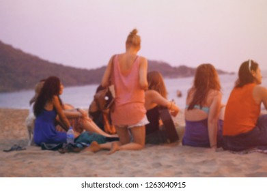 blurred photo of ocean beach with relaxing girls
