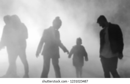 Blurred photo of parents with child and dating couple passing by in fog. Relations abstract background. Black and white photo