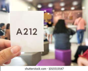 blurred photo of people showing queue ticket while waiting for the service at the bank