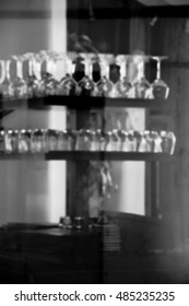 Blurred photo of restaurant interior seen through the window. Black and white.
