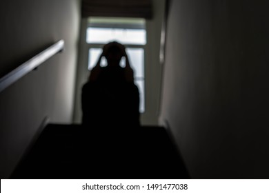 blurred photo of a sad young man Sitting at the stairs in the dark, The sun is in sorrow, Life problems, illness.