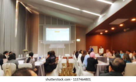 Blurred photo of seminar room. The attendees are brainstorming about meeting topics.